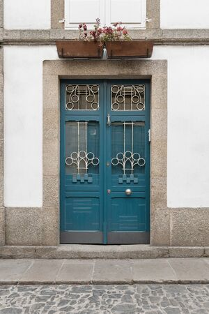 Antique door on building facade made of wood wrought iron and glass. Modernist architecture, Galicia, Spain