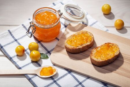 Pot of homemade sweet jam and toasts on wooden table. Delicious marmalade still life Stock Photo