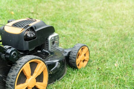 Lawn mower on green grass with copy space for text. Garden work concept background Stock Photo
