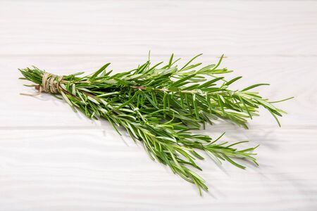 Fresh Rosemary on white wooden background. Rosmarinus officinalis