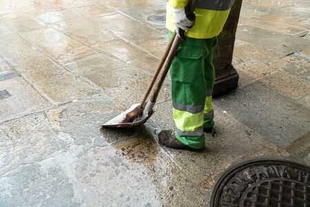 Street sweeper with broom and shovel waiting to work on rainy day. Public cleaning concept Reklamní fotografie