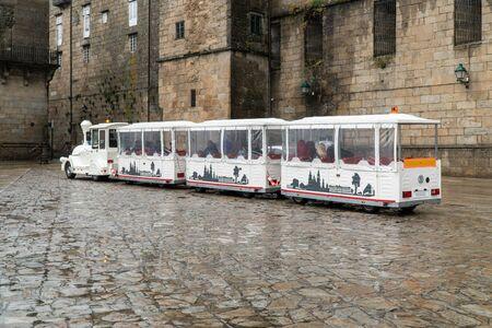 Tourist road train on Obradoiro square on a rainy day. Santiago de Compostela tourism