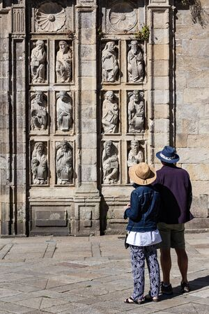 Tourists looking at ancient sculptures of Holy Door of Santiago de Compostela Cathedral. Statues from 15th century Stock Photo - 130117272