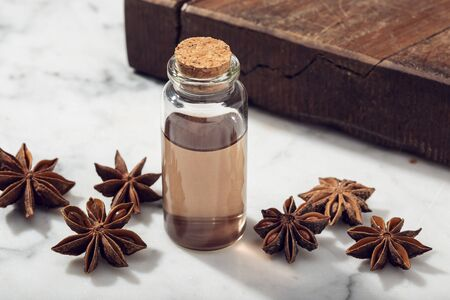 Star anise essential oil on marble table. Illicium verum oil bottle