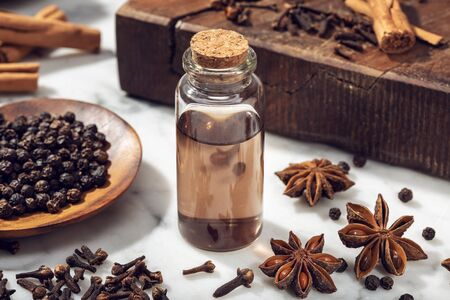 Aromatic seeds essential oil on glass bottle. Cinamon, anise, peppercorn, clove oil for weelness, spa, aromatherapy