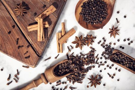 Set of spices on marble table. Star anise, cinnamon, clove and black pepper for cuisine. Top view Imagens