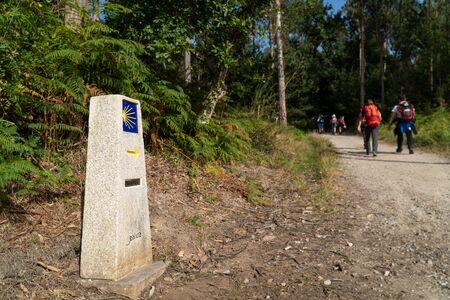 Way of St. James milestone and unfocused pilgrims at background. Yellow scallop sign pilgrimage to Santiago de Compostela