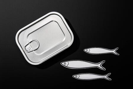 Fish conserve concept. Tin can and paper sardines on black background