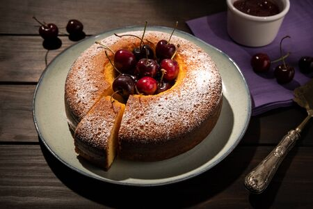 Round cherry cake in plate on wooden table. Dark food