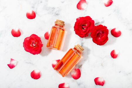 Perfumed Rose Water in glass bottle and small red roses with petals . Massage, aromatherapy and organic cosmetics concept Stok Fotoğraf