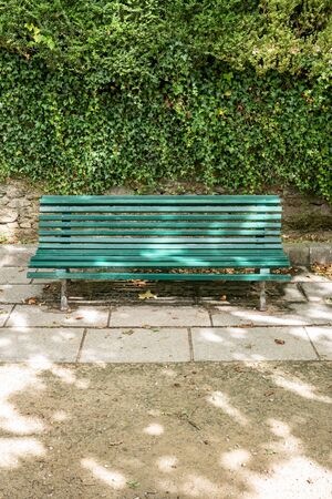 Green wooden bench with a decorative ornate metal legs and armrests on public park. Galicia, Spain