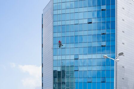 Window cleaner working on a glass facade suspended. Cleaning concept. Copy space