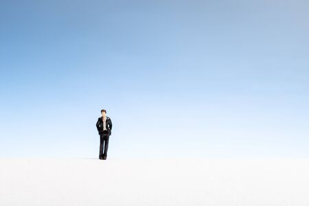 Lonely man concept. Man miniature with suit and tie on abstract space. Copy space