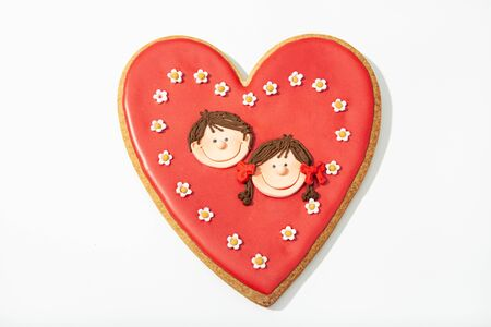 Valentine gift cookie. Red heart cookie with two children face inside. Love concept Banco de Imagens