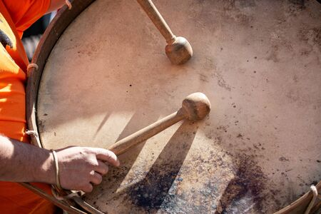 Musician hands with drum sticks playing a bass drum during an outdoor festival. Spanish culture