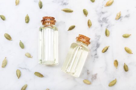 Cardamom essential oil on marble table. Elettaria cardamomum. Top view