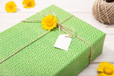 Green Gift or present box with blank label and daisy flowers on table. Mock up