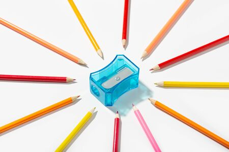 Multicolored pencils and sharpener isolated on white background. Copy space for text. Back to school concept