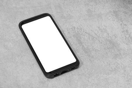 Smart phone with white screen isolated on textured concrete background. Mock up template. Copy space