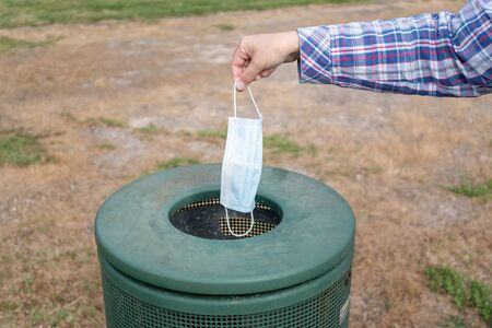 Female hand throwing Medical face mask in the trash can of a park. Single use face mask. Stockfoto
