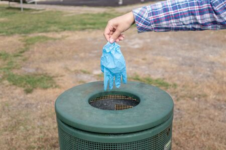 Female hand throwing protective glove in the trash can of a park. Stockfoto - 150207221