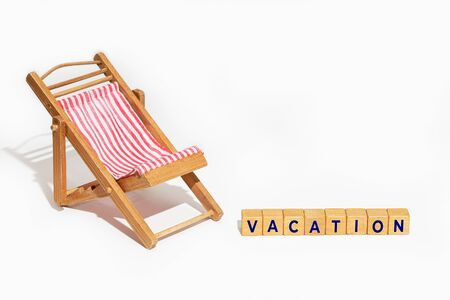Summer vacation concept. Chair and wooden blocks with text Vacation isolated on white background. Copy space