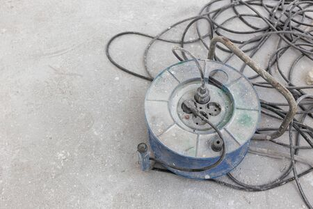 Dirty Electrical extension cord or cable spool with plugs on construction site. Tangled electrical wire. Copy space