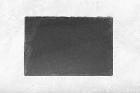 Empty Black slate Tray Plate isolated on white textured background. Top view Mock up Foto de archivo