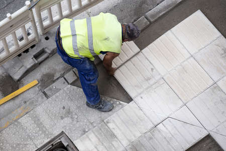 Construction worker laying a tile repairing a sidewalk. Maintenance concept Stock fotó - 155450509