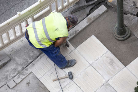 Construction worker with angle grinder repairing a sidewalk. Maintenance concept Stock fotó - 155450629