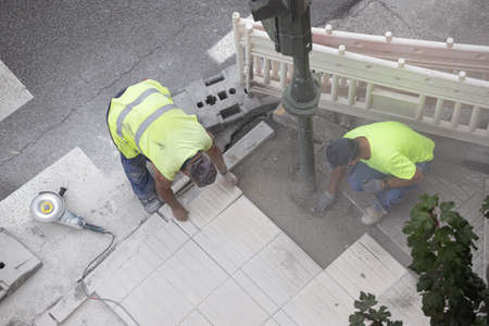 Construction workers repairing a sidewalk. Maintenance concept Stock fotó - 155450971