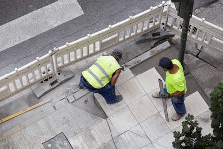 Construction workers repairing a sidewalk. Maintenance concept