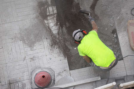Construction worker repairing a sidewalk. Maintenance concept Stock fotó - 155450528
