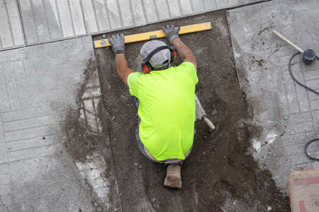 Construction worker with construction level working on a sidewalk. Maintenance concept