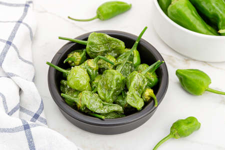 Cooked Padron peppers in a a bowl on marble table. Traditional Spanish appetizer