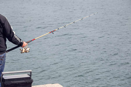 Fisherman standing on edge of dock with fishing rod near sea on Sunny day. Copy space