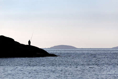 Silhouette of a Fisherman standing on rocks with fishing rod near sea on Sunny day. Copy space