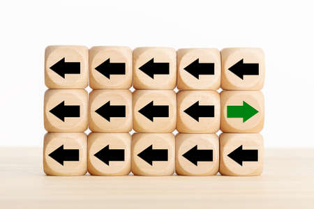 Green arrow pointing the opposite way disruptive from the black arrows in wooden blocks. Think different, unique or independent concept