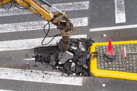 Construction Machine jackhammer breaking asphalt of the road. City Road reparation.