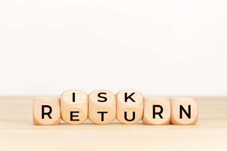 Risk Return concept. Wooden block with text on table. Copy space