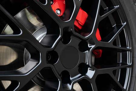 Black Wheel rim and red brake caliper of a sport car. Close up