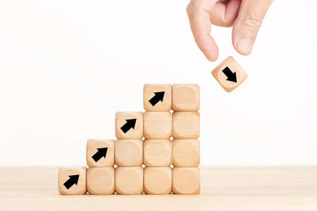 Hand and wooden block with falling arrow. Stock market collapse or financial economy crisis concept. Business uncertainty concept and risk idea. Copy space