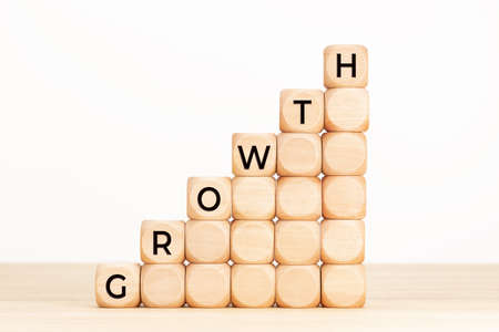 Growth concept. Text in wooden dices on table. White background. Copy space