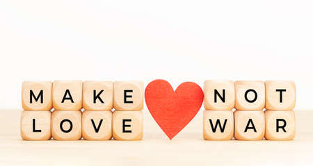 Make Love not War concept. Wooden blocks with text and heart on table. Copy space Stock fotó