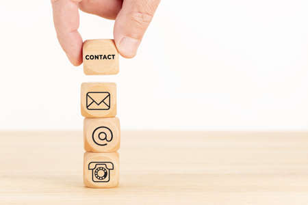 Contact us concept. Hand holding a wooden block with text and a pile of dices with communication icon. Copy space