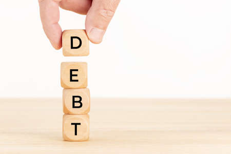 Debt concept. Hand holding a pile of Wooden blocks on table. White background. Copy space