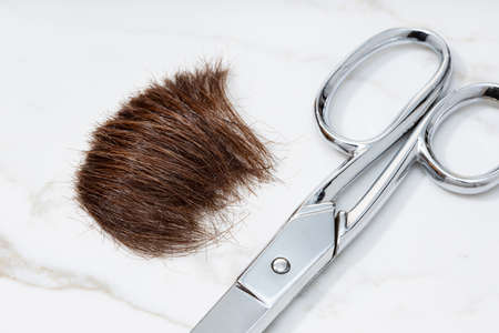 Brown Lock of hair and scissors on marble table. Hairstyle or haircut concept. Close up