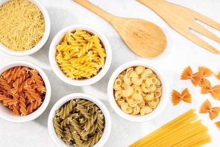 Top view of bowls with assorted uncooked pasta. Mediterranean food