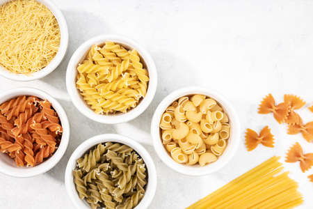 Top view of bowls with assorted uncooked pasta. Mediterranean food. Copy space