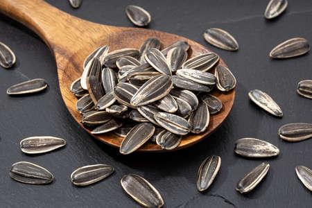 Sunflower Seeds in spoon on black slate. Helianthus seed Stock fotó